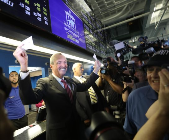 Governor Phil Murphy holding betting ticket in New Jersey sportsbook